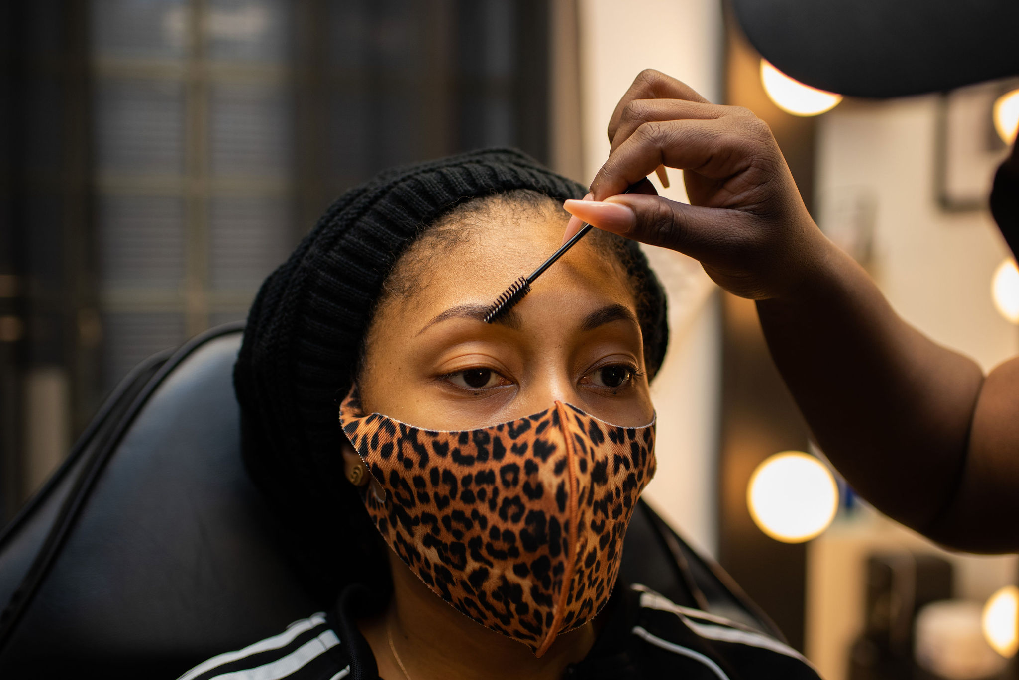 shop owner combing eyebrows before treatment
